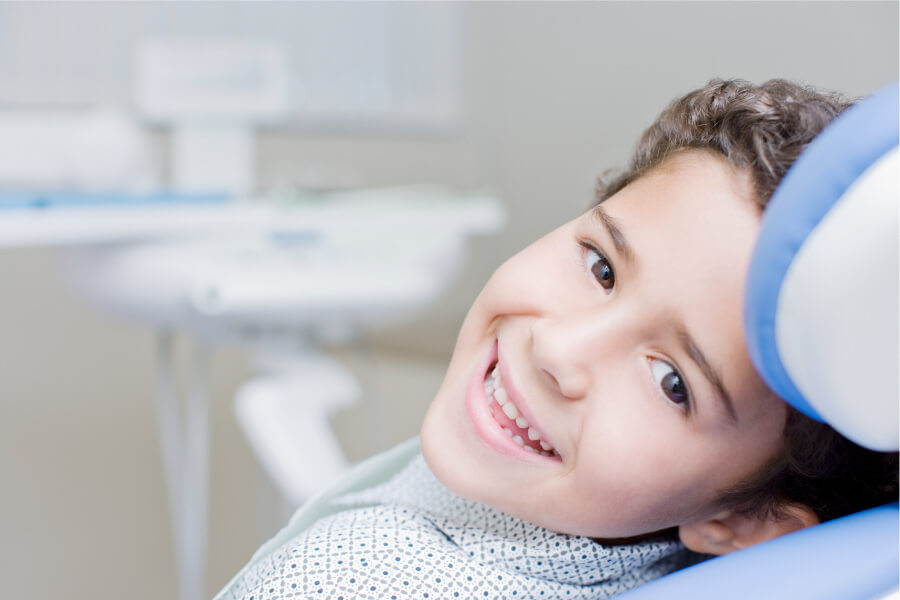 Brunette boy smiles while sitting in the treatment chair at his pediatric dentist in Austin, TX
